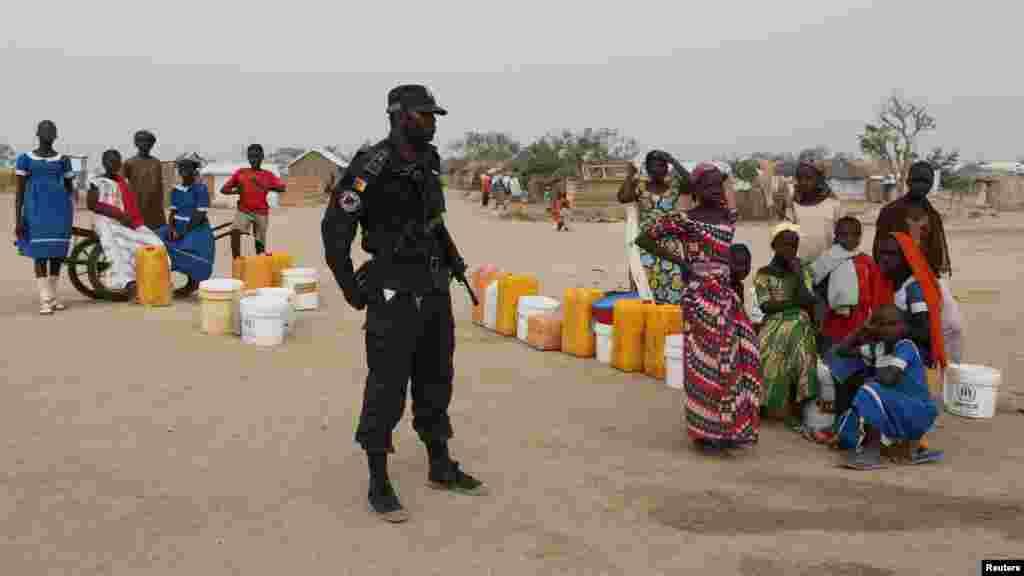 Un policier camerounais à côté des gens qui attendent de remplir leurs bidons d'eau dans un camp de réfugiés à Minawao au Cameroun, le 15 mars 2016.