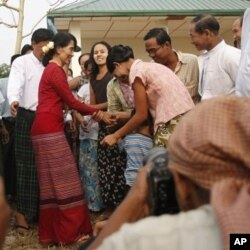ປະຊາຊົນພາກັນຄໍານັບຮັບຕ້ອນ ທ່ານນາງ Aung San Suu Kyi ຢູ່ບ່ອນປ່ອນບັດແຫ່ງນຶ່ງ ໃນນະຄອນຢ່າງກຸ້ງ, ວັນອາທິດ ທີ 1 ເມສາ 2012.