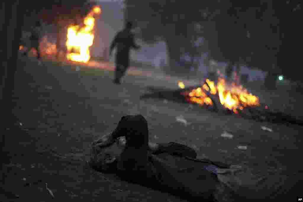 Một người biểu tình Ấn Độ bị choáng ngộp bởi hơi cay nằm trên mặt đất tại thủ đô New Delhi, ngày 23/12/2012.