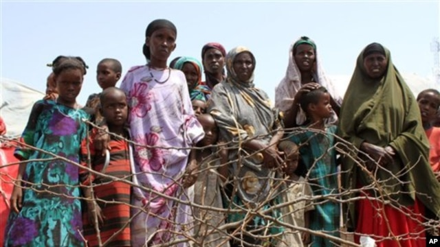 Women and children stand at the edge of an impromptu camp of internally displaced people that has sprung up near the airport, Mogadishu, July 27, 2011