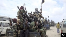 FILE - Al-Shabab fighters display weapons as they conduct military exercises in northern Mogadishu, Somalia.