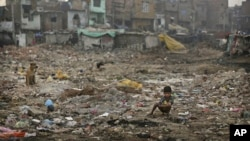 FILE- An Indian boy defecates in the open in a poor neighborhood of New Delhi, India, Nov. 6, 2012.