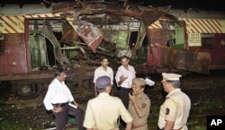 FILE - Police investigate near a train destroyed by a bomb blast at Mahim railway station in Mumbai, India, July 11, 2006.
