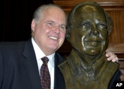 FILE - Conservative commentator Rush Limbaugh poses with a bust in his likeness during a ceremony inducting him into the Hall of Famous Missourians in the state Capitol in Jefferson City, May 14, 2012.