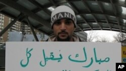 Saudi national Menyar al-Mufti displays an anti-Mubarak sign while in transit between two Washington protests, one at the Egyptian embassy and the other at the White House.
