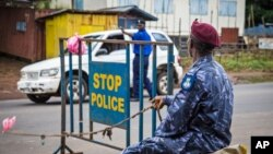 Cảnh sát gác tại một chốt chặn trong khi chính phủ Sierra Leone phong tỏa đường phố ba ngày để kiểm soát dịch Ebola, ngày 19 tháng 9, 2014.