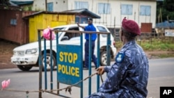 Police guard a roadblock as Sierra Leone government enforces a three day lock down on movement of all people in an attempt to fight the Ebola virus in Freetown, Sierra Leone, Sept. 19, 2014.