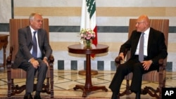 In this photo released by Lebanon's official government photographer Dalati Nohra, Lebanese Prime Minister Tammam Salam, right, meets with French Foreign Minister Jean-Marc Ayrault at the government House, in Beirut, Lebanon, July 12, 2016.