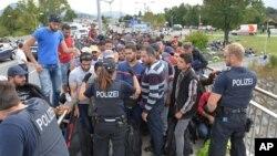La police encadre des réfugiés à Salzburg à la frontière entre l'Autriche et l'Allemagne, 17 septembre 2015.