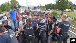 Echanges entre la police allemande et des réfugiés sur le territoire autrichien. Le forces de sécurité allemandes ont arrêtés les migrants sur un pont à la frontière entre l'Autriche et l'Allemagne à Salzbourg, jeudi 17 septembre, 2015. (AP Photo / Kerstin Joensson)