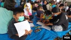 Kegiatan menggambar dan mewarnai oleh anak-anak penyintas gempa di shelter Terintegrasi di Stadion Manakarra, Mamuju, Sulawesi Barat. Minggu, 31 Januari 2021. (Foto: Yoanes Litha/VOA)