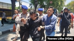 Polisi mengamankan seorang mahasiswa yang diduga menjadi pelaku pelemparan batu terhadap petugas dalam aksi demonstrasi penolakan RKUHP dan pelemahan KPK di Kota Palu, 25 September 2019. (Foto: VOA/Yoanes Litha)