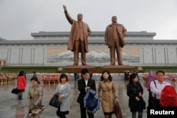 People walk away after paying their respects at the statues of North Korea founder Kim Il Sung, left, and late leader Kim Jong Il in Pyongyang, North Korea, April 14, 2017.