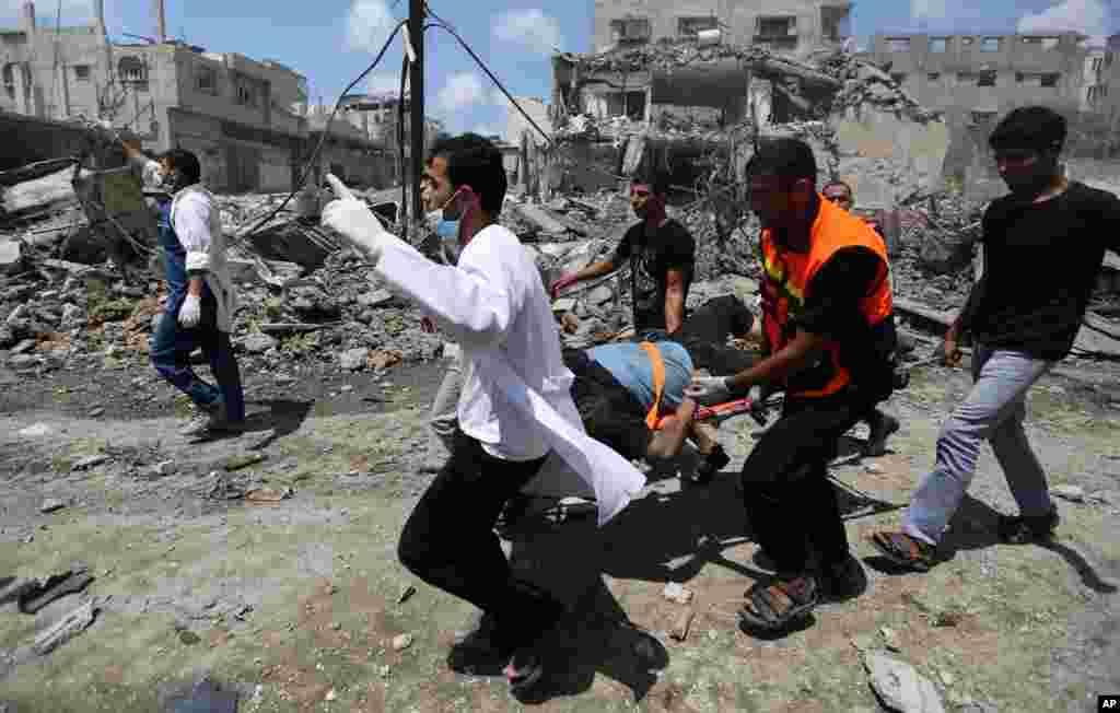 امدادگران فلسطینی به مجروحان در محله شجاعیه در شمال غزه یاری میرسانند. شجاعیه در جریان عملیات زمینی اسرائیل زیر آتش قرار گرفت. 20 ژوئیه