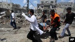 7月20日在加沙希贾亚地区巴勒斯坦救护人员用担架抬着一名伤员