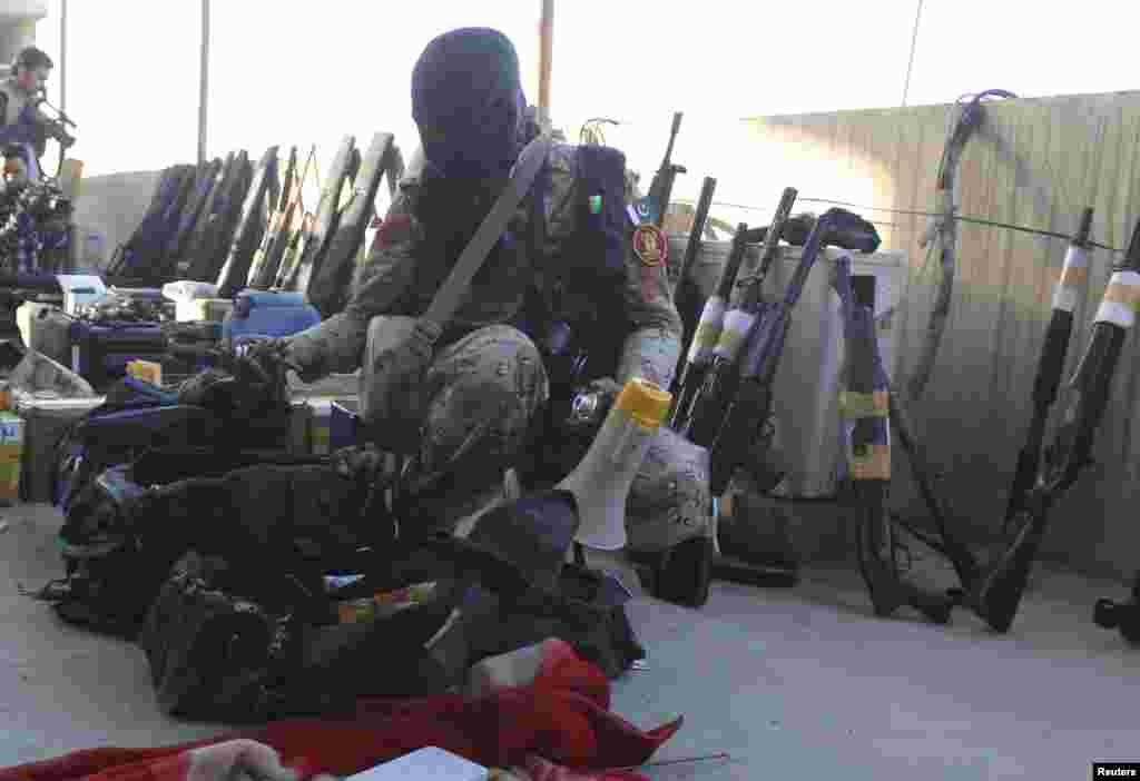A paramilitary soldier displays weapons recovered during a raid on the Muttahida Qaumi Movement (MQM) political party's headquarters in Karachi March 11, 2015. A Pakistani paramilitary force raided the headquarters of a major political party on Wednesday