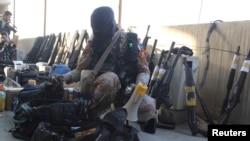 Binh sĩ bán quân sự Pakistan bên cạnh các loại vũ khí tịch thu được trong một cuộc tấn công vào đại bản doanh của đảng MQM ở Karachi, ngày 11/3/2015.