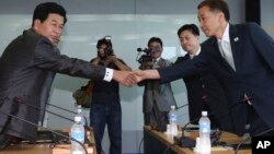 Kim Kiwoong, right, the head of South Korea's working-level delegation, shakes hands with his North Korean counterpart Park Chol Su, left, before their meeting at Kaesong Industrial District Management Committee in Kaesong, North Korea, August 14, 2013.