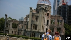 Foreign visitors rest near Atomic Bomb Dome in Hiroshima, western Japan, Aug. 5, 2015.