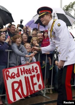 Britain's Prince Harry reacts with members of the public displaying a sign reading 'Red Heads Rule' after visiting the Australian War Memorial in Canberra, April 6, 2015.
