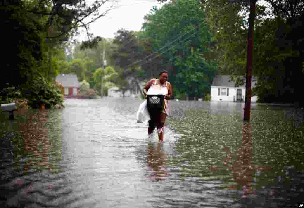 Leandra Felton wades through rising floodwaters with items from her home in Memphis, Tennessee May 7. (Reuters)