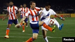 FILE - Diego Fernando Nadaya (R) of Mumbai City FC fights for the ball with Jose Miguel Gonzalez Rey (2nd R) of Atletico de Kolkata during the opening match of the Indian Super League soccer tournament at Salt Lake stadium in Kolkata, Oct. 12, 2014.