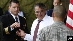 """美國國防部長萊昂.帕內塔(中)準備給駐紮在橫田空軍基地美國軍事人員一枚""""挑戰硬幣""""。"""