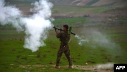 FILE - An Afghan National Army (ANA) soldier fires a rocket-propelled grenade (RPG) during a military operation in Badghis Province.