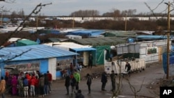 Converted shipping containers are placed at the entrance of the Calais refugee camp. Some refugees tried to force their way aboard a British ferry at the port city.