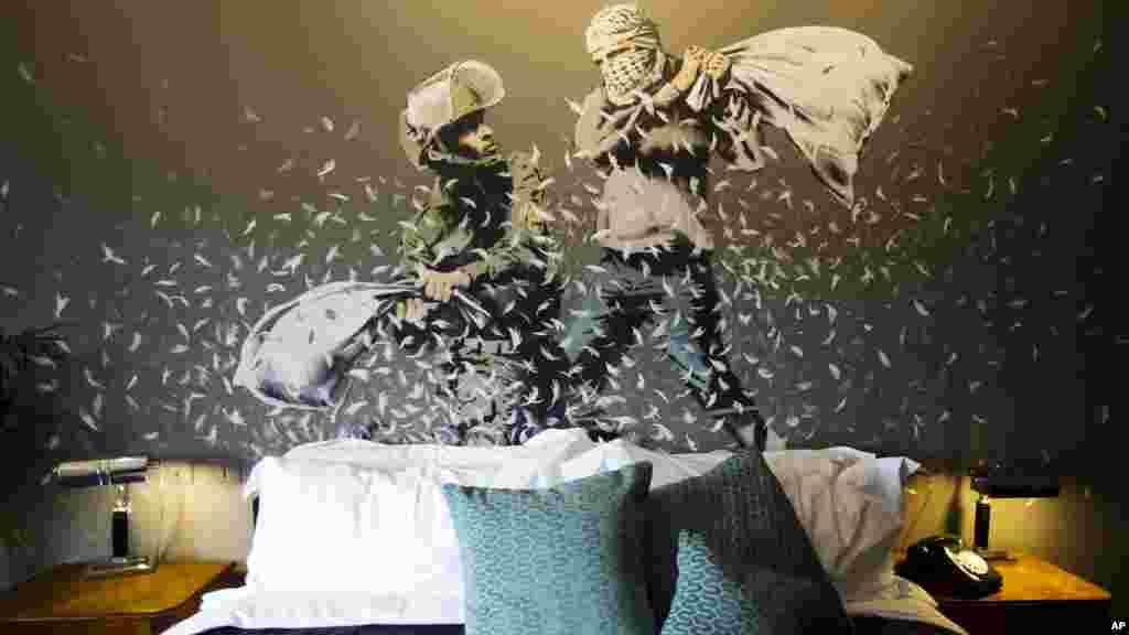 គំនូរនៅលើជញ្ជាំងរបស់លោក Banksy បង្ហាញឲ្យឃើញប៉ូលិសការពារព្រំដែនអ៊ីស្រាអែលម្នាក់ និងជនជាតិប៉ាឡេស្ទីន វាយគ្នាដោយប្រើខ្នើយក្នុងបន្ទប់ «សណ្ឋាគារដែលខ័នដោយជញ្ជាំង» នៅទីក្រុង Bethlehem នៃតំបន់ West Bank។