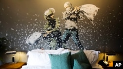 "A Banksy wall painting showing Israeli border policeman and Palestinian in a pillow fight is seen in one of the rooms of the ""The Walled Off Hotel"" in the West Bank city of Bethlehem, March 3, 2017."