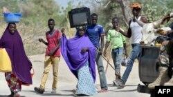 Des réfugiés fuyant la localité nigériane de Malam Fatori, près des frontières du Nigeria avec le Niger et le Tchad,passent devant une patrouille de soldats nigériens pour se rendre à Bosso, au Niger, le 25 mai 2015.