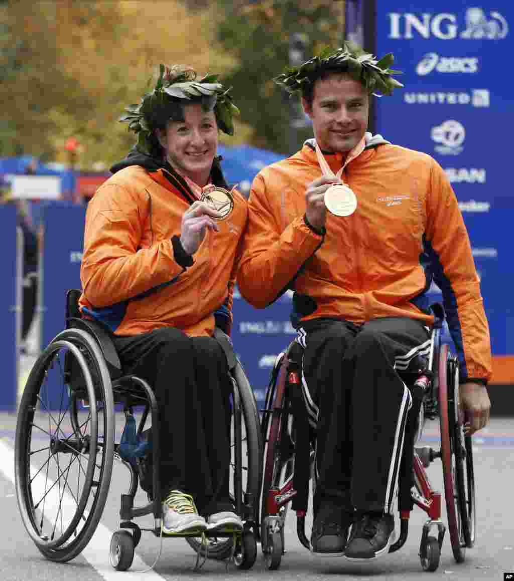 Women's wheelchair winner Tatyana McFadden of Maryland, left, and men's wheelchair winner Marcel Hug of Switzerland pose for photographers after winning their divisions in the New York City Marathon, Nov. 3, 2013, in New York.
