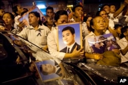 FILE - Cambodian mourners cry and pray outside a crematorium as the late King Norodom Sihanouk is cremated in Phnom Penh, Cambodia, Monday, Feb. 4, 2013.