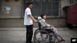 Di foto yang diambil tanggal 30 Juni 2010 ini, Ni Yulan (duduk di kursi roda) dibantu Don Jiqin, suaminya, menikmati udara sore Beijing (Foto: dok). Mahkamah banding Tiongkok membatalkan vonis penipuan atas pengacara aktivis difabel Ni Yulan yang dipenja