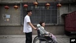Pada foto yang diambil tanggal 30 Juni 2010 ini, Ni Yulan (duduk di kursi roda) dibantu Don Jiqin, suaminya, menikmati udara sore Beijing (Foto: dok).