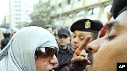 An Egyptian activist shouts at anti-riot policemen who block the way leading to the journalists syndicate in downtown Cairo.