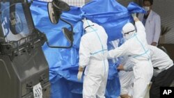 Japan's Self-Defense Force's members and others in protective gear help to transfer workers who stepped into contaminated water on Thursday during their operation at the Fukushima Daiichi nuclear plant, March 25, 2011