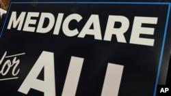 2019年4月10日在华盛顿国会山举行的一次新闻发布会上的``全民医保''标语牌。