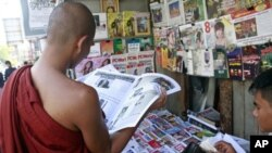 A Buddhist monk reads a journal at a roadside shop in Rangoon, Burma, Tuesday, Feb. 28, 2012.