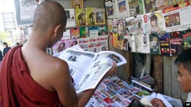 A Buddhist monk reads a journal at a roadside shop in Rangoon, Burma, Tuesday, Feb. 28, 2012.