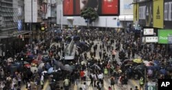 A large group of protesters took over a major street in a Hong Kong shopping district late Sunday afternoon, setting up barricades to block off the area and defend it against police.
