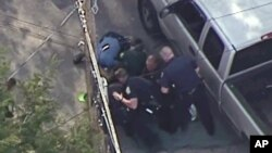 This aerial image made from a helicopter video provided by WHDH shows several officers allegedly pummeling Richard Simone, who had exited his vehicle after a high-speed police pursuit, in Nashua, New Hampshire, May 11, 2016.