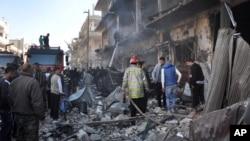 Warga Suriah dan tim pemadam kebakaran berkumpul di sekitar lokasi serangan bom di Zahraa, provinsi Homs, Suriah (28/12). Ledakan tersebut terjadi pada saat ratusan pejuang dan anggota keluarga mereka tengah dievakuasi dari tiga lokasi di Suriah menuju Lebanon dan Turki.