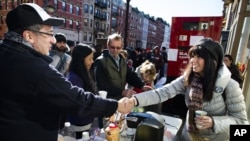 Felice Vazquez greets a neighbor as she mans a table providing hot drinks and snacks on Washington Street as the buildings around them remain without power due to damage caused by Superstorm Sandy in Hoboken, New Jersey, November 4, 2012.
