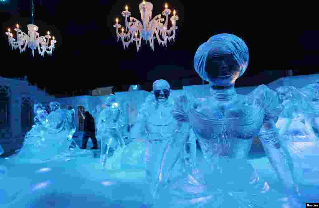 """A sculptor walks past sculptures based on characters from Disney movies at the Snow and Ice Sculpture Festival in Bruges. Some 28 artists from all over the world made 55 sculptures out of 250 tons of ice depicting Disney's newest movie """"Frozen"""". The festival will open on Nov. 22."""