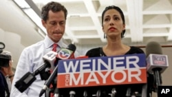 New York mayoral candidate Anthony Weiner, left, listens as his wife, Huma Abedin, speaks during a news conference at the Gay Men's Health Crisis headquarters, July 23, 2013, in New York.