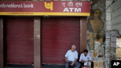 A security guard, right, reads a newspaper as he sits in front of a closed ATM in New Delhi, India, April 18, 2018. Several ATMs were seen to have run dry across the country, reportedly from a surge in demand of cash withdrawals.