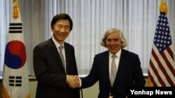 윤병세 한국 외교장관(왼쪽)과 어니스트 모니즈 미국 에너지부 장관이 15일 미국 워싱턴DC 에너지부 본부에서 개정된 한미 원자력협정문에 서명한 뒤 악수하고 있다.