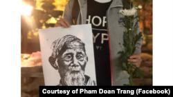 Một thanh niên ở Hà Nội cầm tấm hình ông Lê Đình Kình tại lễ tưởng niệm hôm 12 tháng Giêng. (Photo courtesy of Facebook user Pham Doan Trang)